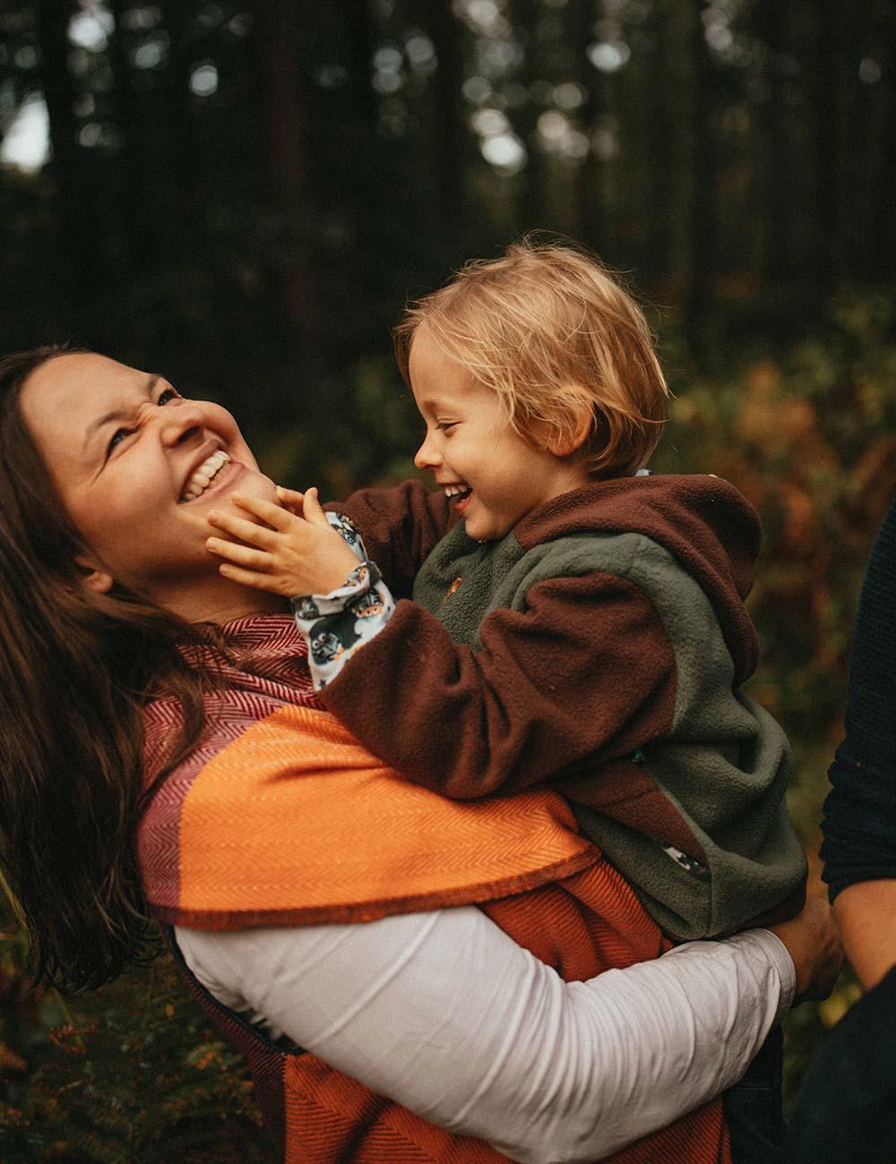 Mutter und Kind im Arm lachen zusammen.